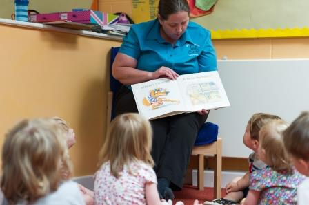 Nursery staff reading to children